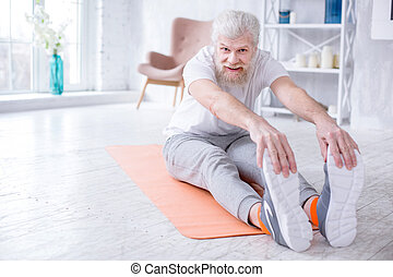 Handsome elderly man bending forward and touching toes