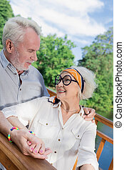 Handsome elderly man hugging his beautiful wife and looking at her