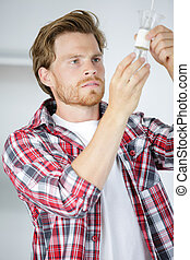 handsome electrician changing classical bulb