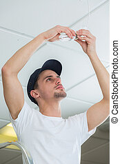handsome electrician changing lightbulb