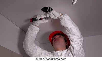 Handsome electrician in protective workwear remove cable...