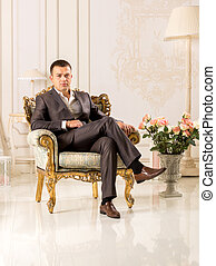 man in black suit sitting in luxurious chair at classic interior