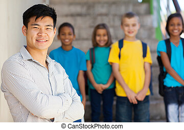 handsome male elementary educator with students on background