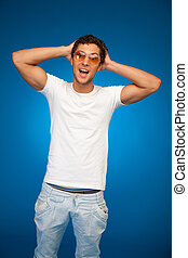 handsome emotional boy wearing sunglasses over blue