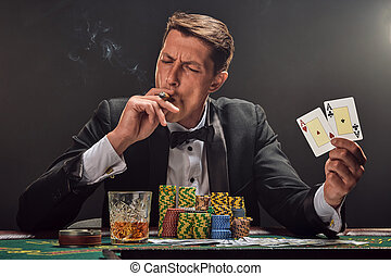 Handsome emotional man is playing poker sitting at the table in casino against a white spotlight.