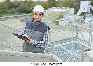 handsome engineer with clipboard near the factory