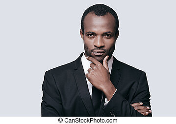 Handsome entrepreneur. Portrait of confident young African man holding hand on chin and looking at camera while standing against grey background
