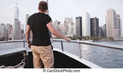 Handsome excited traveler man with arms wide open enjoying amazing New York skyline on a river tour boat slow motion.