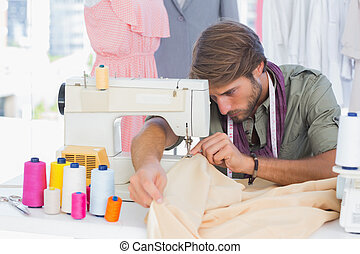Handsome fashion designer sewing with a sewing machine