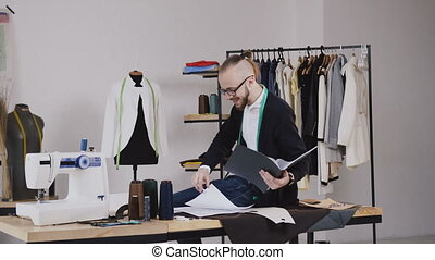 Handsome fashion designer sitting on table in atelier and holds a folder with sketches, he makes notes in his notebook. Young bearded tailor in glasses dressed in white shirt and black blouse with measure tape on neck working in atelier