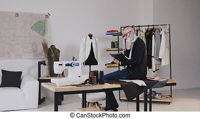 Handsome fashion designer sitting on table in atelier and talking phone, he makes notes in his notebook. Young bearded tailor in glasses dressed in white shirt and black blouse with measure tape on neck working in atelier and talking phone