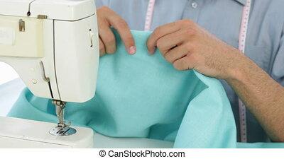Handsome fashion designer using sewing machine in his studio