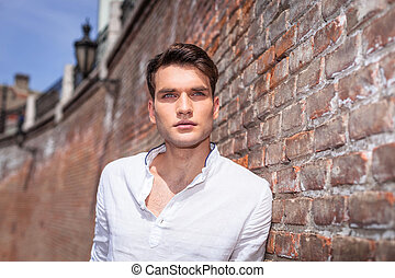 Handsome fashion man leaning on a brick wall