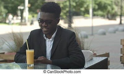 Handsome fashionable afro american business man stirring juice while usinh smartphone in outside cafe