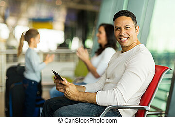 handsome father using tablet computer at airport