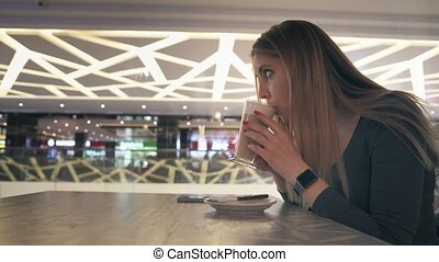 Handsome female is resting at the cafe and drinking hot...