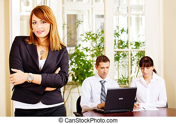 Handsome female manager with employers in office