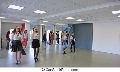 Handsome females train in catwalk in spacious ballroom.