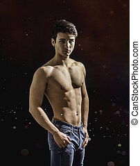 Handsome, fit shirtless young man in jeans