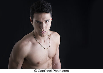 Handsome, fit shirtless young man isolated on black