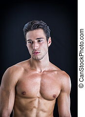 Handsome, fit topless young man isolated on black