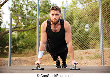 Handsome fitness man doing push-up exercises with sport...
