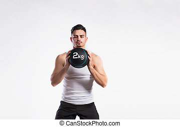 Handsome fitness man holding medicine ball, studio shot.