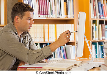 Handsome focused student pointing at computer in library
