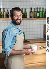 Handsome friendly waiter smiling while holding a cup of coffee and cookies