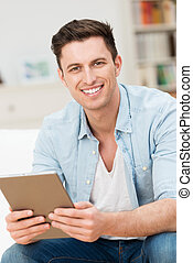 Handsome friendly young man holding a tablet