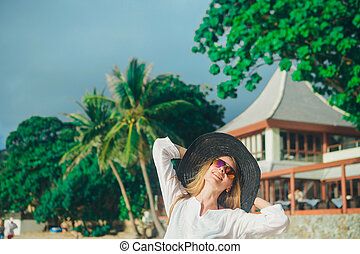 handsome girl in hat on the beach background. Portrait of a woman in white clothes and balck hat