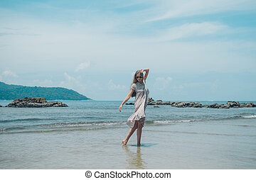 handsome girl on the beach background. Portrait of a woman in white clothes on the sea