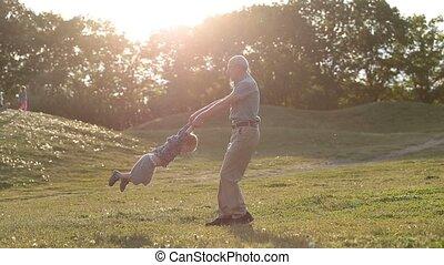 Handsome grandad spinning around toddler boy