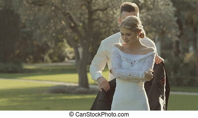 Handsome groom comes  to bride behind her and puts on his jacket