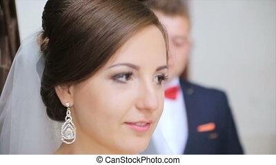 Handsome groom comes to bride behind her