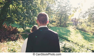 Handsome groom comes to bride with smile in the park. Slowly