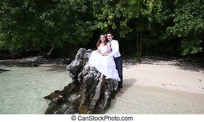 handsome groom embraces brunette bride sitting on rock