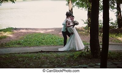 Handsome groom holds his bride in his arms and swirls. Beautiful wedding on a river bank in summertime.