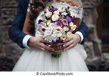 Handsome groom hugging beautiful bride in white dress from behind bouquet closeup