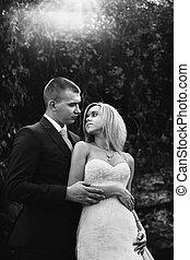 Handsome groom hugging blonde bride from behind in forest b&w