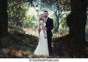 Handsome groom hugging blonde bride in forest at sunset