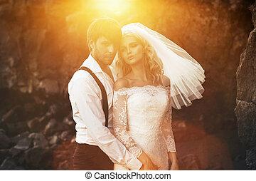 Handsome groom hugging his beautiful wife