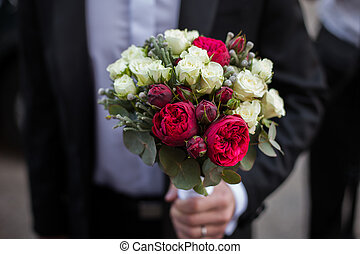 Handsome groom in black suit holding wedding bouquet closeup