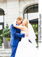 Handsome  groom kissing beautiful bride outdoors