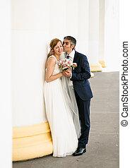 Handsome groom kissing cheerful bride in cheek