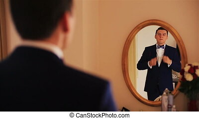 Handsome groom looks on reflection in the mirror and...