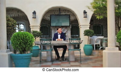 Handsome groom sitting on the cafe outdoors in Montenegro, Budva