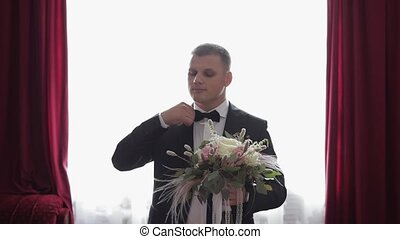 Handsome groom standing near window with a bunch of wedding flowers