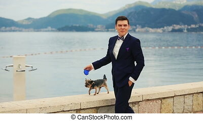 Handsome groom walking the cute yorkshire terrier on sunny quay in Montenegro, Budva close up with beautiful seascape on background