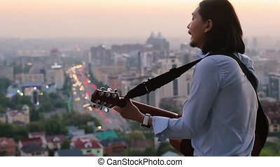 Handsome guitarist playing and singing with passion against a beautiful city landscape